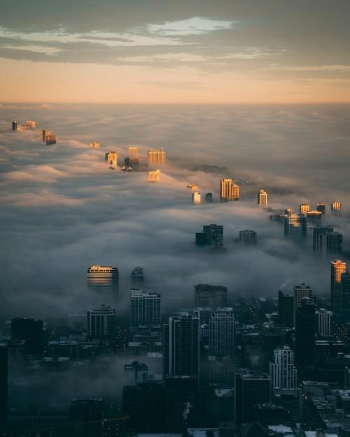 Skyline della città con uno strato di nebbia all'alba visto dall'alto Foto Gratuite