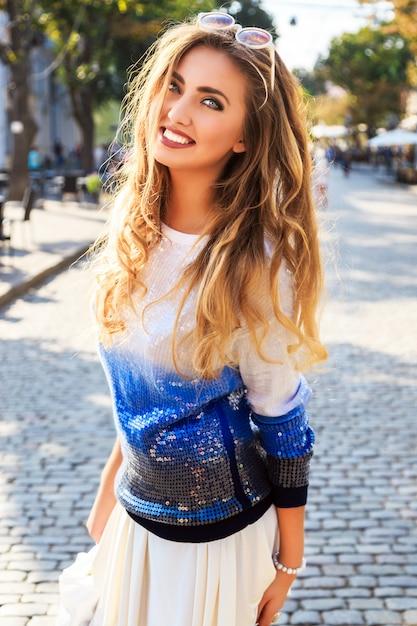 ストリートant素敵な晴れた秋秋の日でポーズ美しい女性の都市のスタイリッシュな肖像画。明るいブルーのカジュアルなセーターとサングラスを着用しています。 無料写真