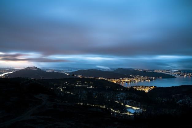 Город в окружении гор и море, покрытое огнями, под пасмурным небом вечером Бесплатные Фотографии