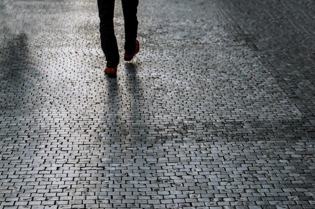 Городской вид на тротуар со спины, человек идет по тротуару в хорошо освещенном месте. темные тени на мощеной улице. Premium Фотографии