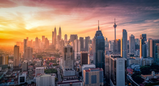 Cityscape of kuala lumpur city skyline with swimming pool on the roof top of hotel at sunrise in malaysia. Premium Photo