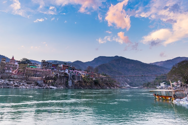 Cityscape of rishikesh at sunset, holy town and travel destination in india. colorful sky and clouds reflecting over the ganges river. Premium Photo