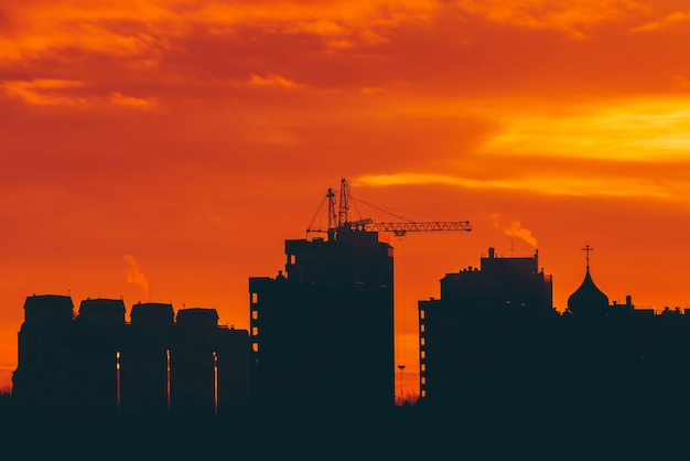 Cityscape with vivid fiery dawn. amazing warm dramatic cloudy sky above dark silhouettes of city buildings. Premium Photo
