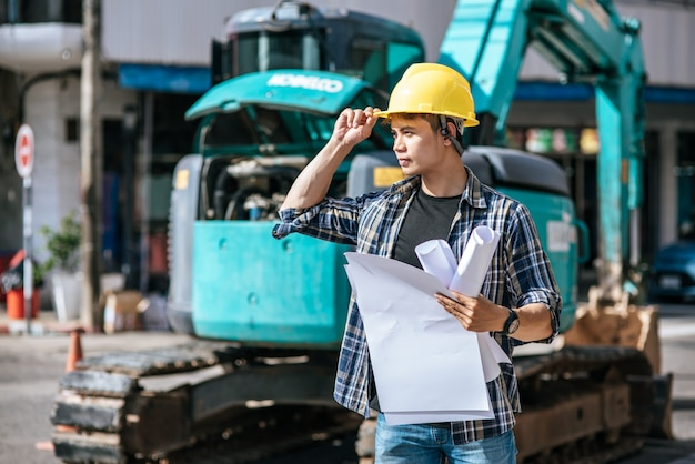 Civil engineers work on large road and machinery conditions. Free Photo