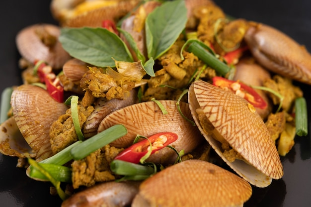 Clams fried curry powder on a black plate. Free Photo