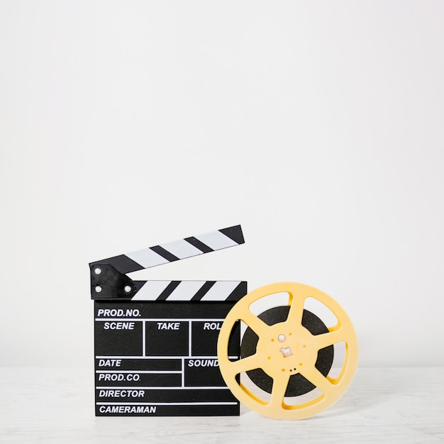 Clapboard with film reel Premium Photo