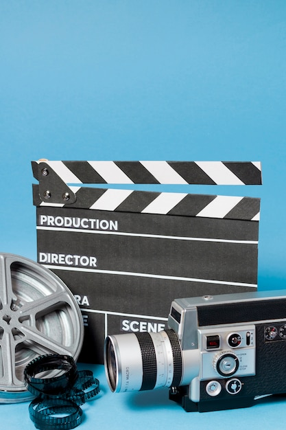 Clapperboard; camcorder camera; film reel and film stripes on blue backdrop Free Photo