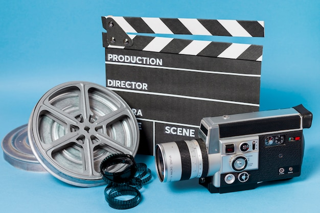 Clapperboard; film reel and camcorder on blue background Free Photo