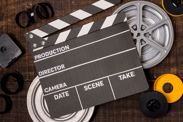 Clapperboard over the film reel and negatives on wooden backdrop Premium Photo