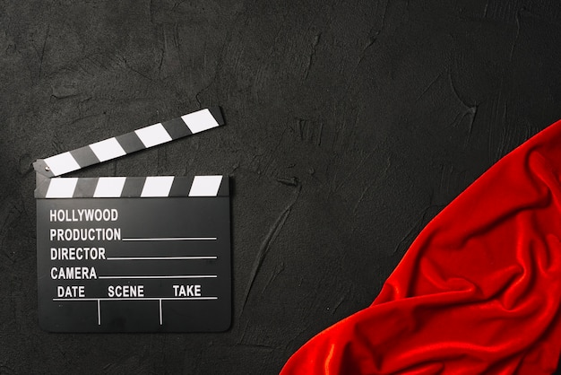 Clapperboard near red cloth Free Photo