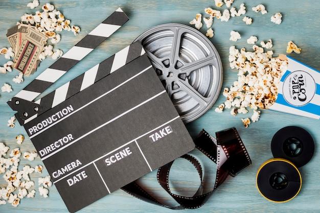 Clapperboard; popcorn; film stripe and cinema tickets on wooden desk Free Photo
