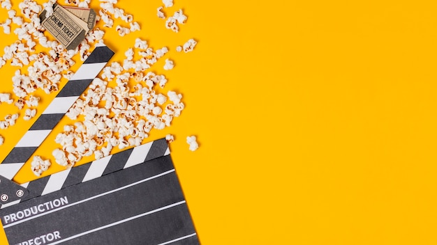Clapperboard; popcorns and cinema tickets on yellow background Free Photo