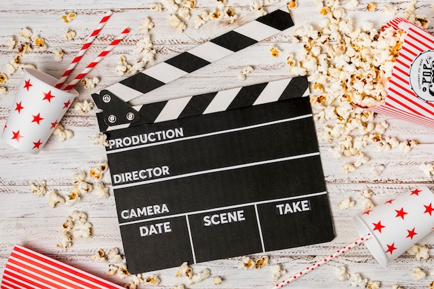 Clapperboard; takeaway glass with drinking straws and popcorns on wooden desk Free Photo