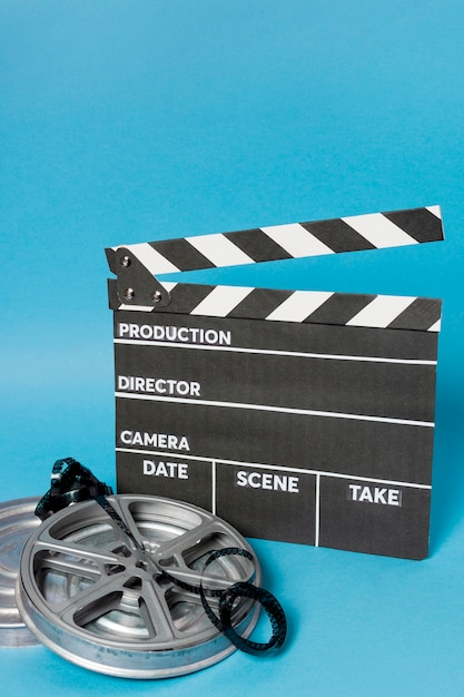 Clapperboard with film reel and film stripes against blue backdrop Free Photo