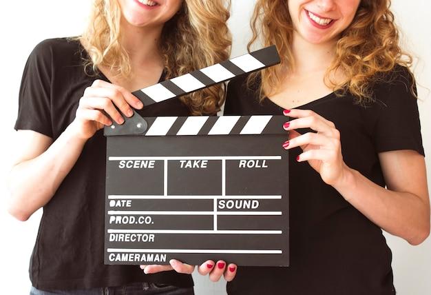 Clapperboardを保持する女性の姉妹の中間セクション 無料写真