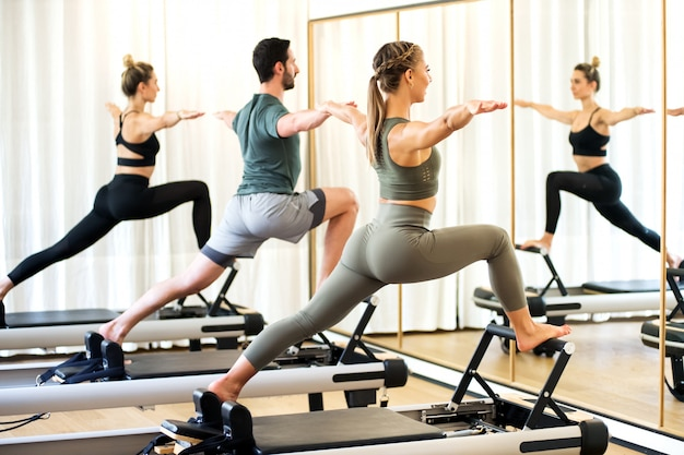 Class in a gym doing pilates standing lunges Premium Photo
