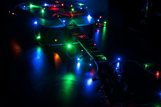 Classic acoustic guitar in christmas holiday lights in memory of music Premium Photo