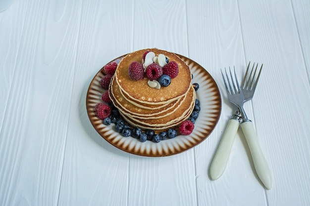 Classic american pancakes with fresh berry on a blue wooden background. pancakes with fruit. summer homemade breakfast. Premium Photo