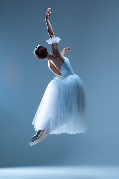 Classic ballerina dancing on blue Free Photo