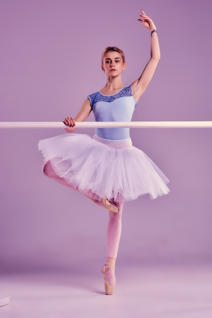 Classic ballerina posing at ballet barre Free Photo