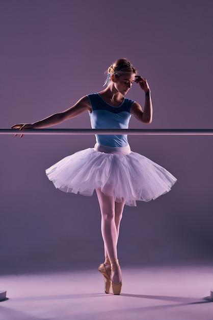 Ballerina classica che propone alla sbarra di balletto Foto Gratuite