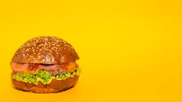 Classic beef burger with yellow backbround Free Photo