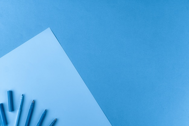 Classic blue colored top view photo of scattered stationery Premium Photo