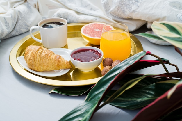 Classic breakfast in bed, hotel service. coffee, jam, croissant, orange juice, grapefruit, lychee. Premium Photo