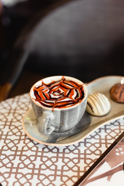 Classic caramel cappuccino with cookies Free Photo