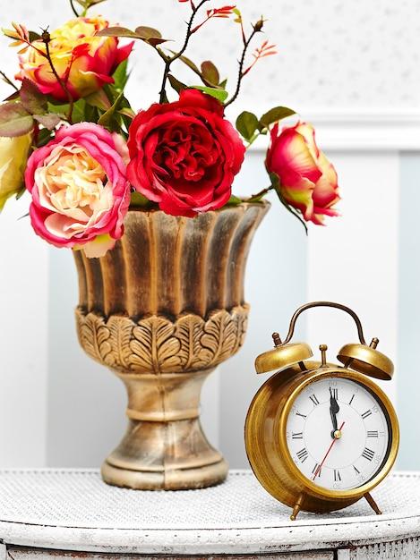 Классические часы-часы в ярком красочном ретро интерьере за красными цветами Бесплатные Фотографии