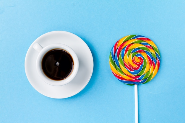 Classic cup coffee espresso with candy lollypop breakfast on bright blue table background Free Photo