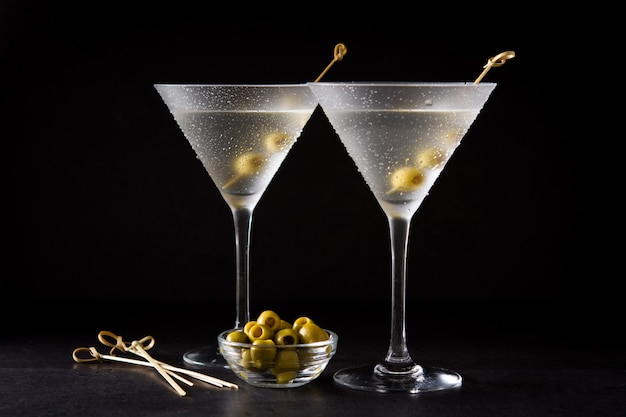 Classic dry martini with olives on black Premium Photo