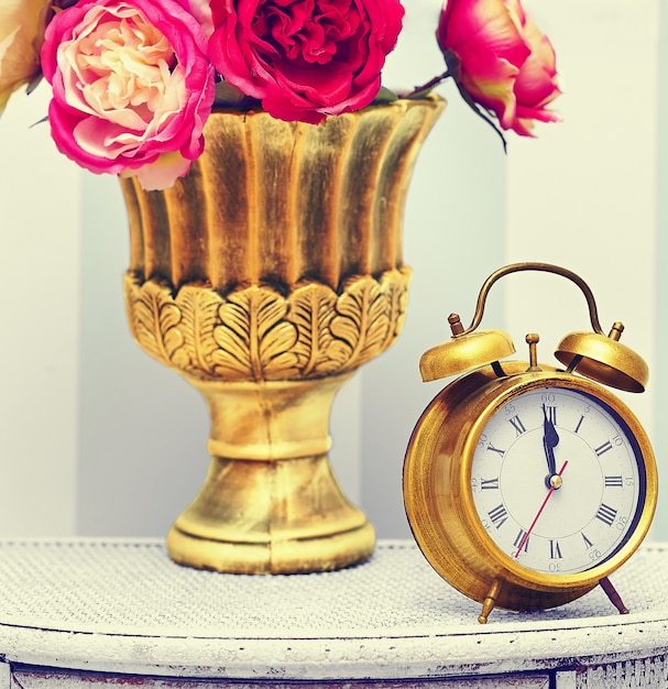 Classic gold clock  watch in bright colorful retro interior behind red flowers Free Photo