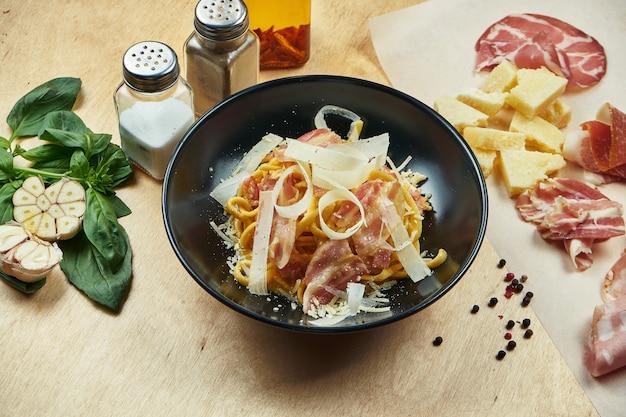 クラシックな自家製カルボナーラパスタ。ベシャメルソース、ベーコン、パルメザンチーズをブラックボウルに入れたもの。伝統的なイタリア料理 Premium写真