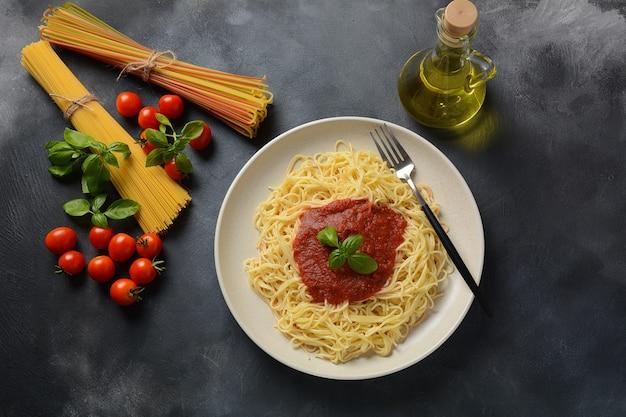 古典的なイタリアのスパゲッティパスタとトマトソースとバジルのプレート Premium写真