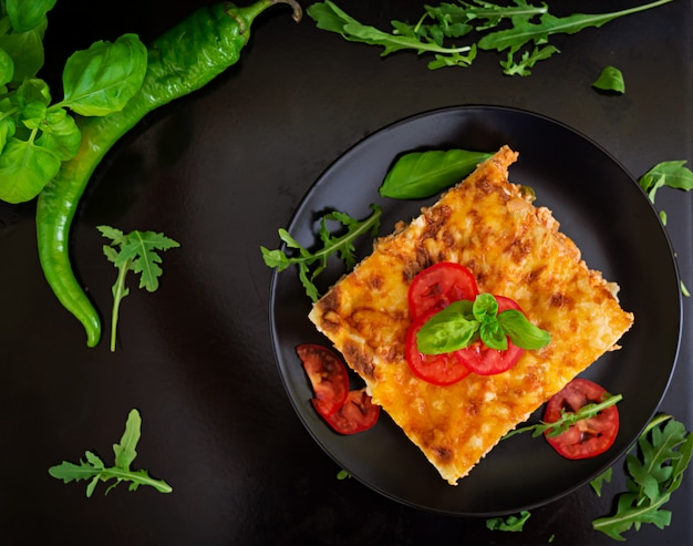 Classic lasagna with bolognese sauce on dark surface Premium Photo