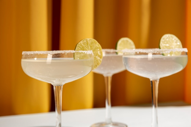 Classic lime margarita cocktail with sliced limes against yellow curtain Free Photo