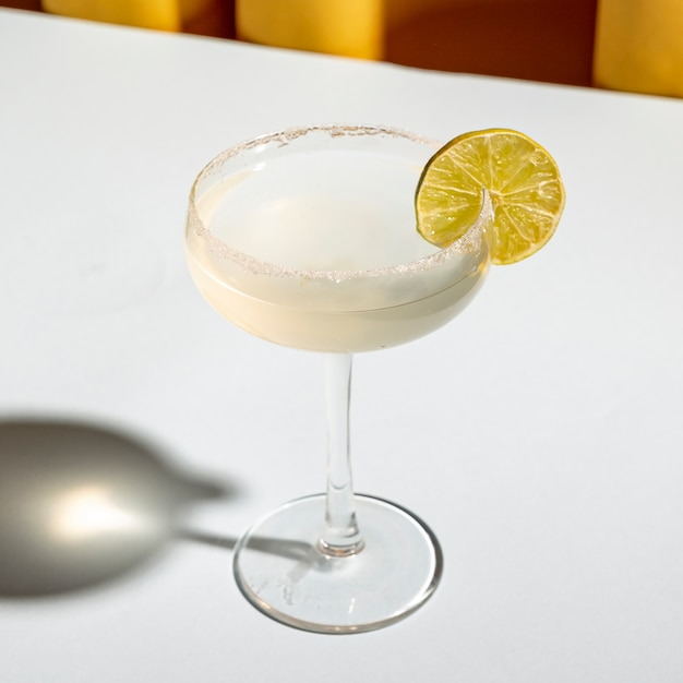 Classic margarita cocktail with salt on the edge of saucer glass on white table Free Photo
