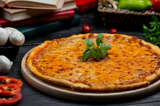 Classic margarita pizza with full melted cheddar and fresh basilica leaves Free Photo