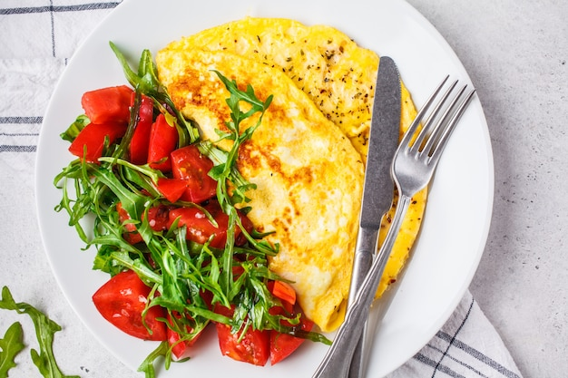 Classic omelet with cheese and tomatoes salad on white plate, top view. Premium Photo