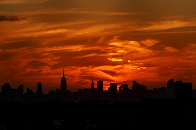 A classic photo of a scenic sunset with the skyscrapers of new york city Premium Photo
