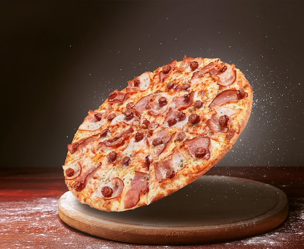 Classic pizza on a dark wooden table surface and a scattering of flour. pizza restaurant menu concept Premium Photo