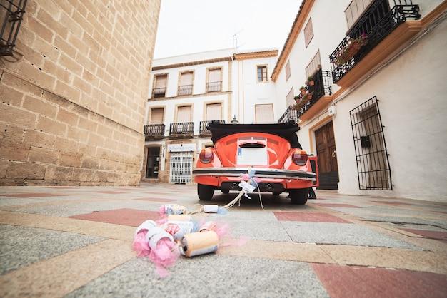 Classic retro red wedding car and newlyweds inside. Premium Photo