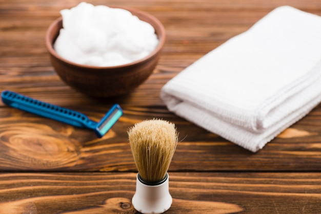 Classic shaving brush in front of foam bowl; folded white napkin and razor on wooden desk Free Photo