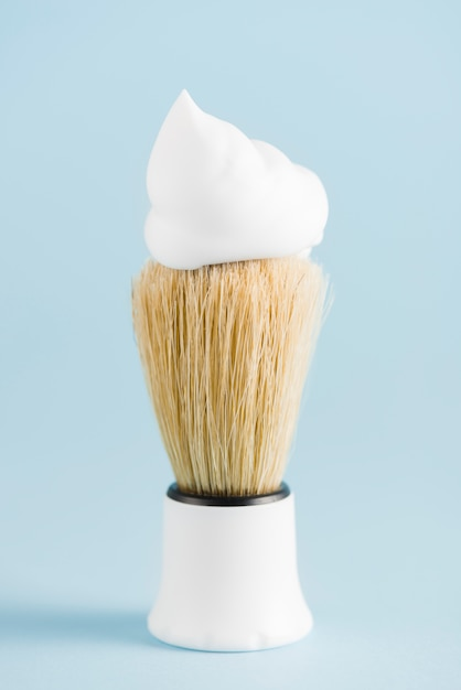 The classic shaving brush with foam against blue backdrop Free Photo