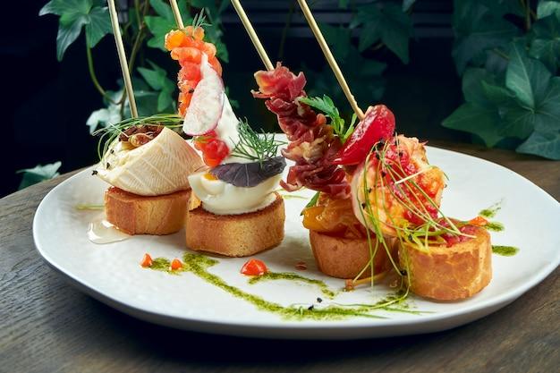 古典的なスペインの前菜-エビ、カマンベール、サーモン、ハモンの白い皿にピンチョスまたはタパス。セレクティブフォーカス Premium写真