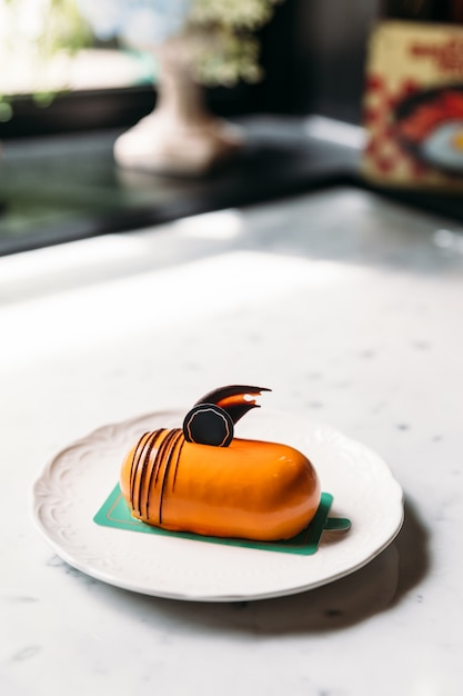 Classic thai tea mousses cake decorated with chocolate in white plate on marble top table. Premium Photo