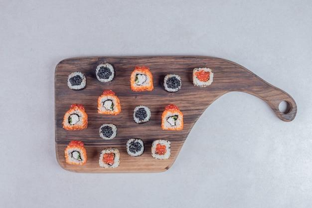 Classici tre tipi di rotoli di sushi su sfondo bianco con le bacchette. Foto Gratuite