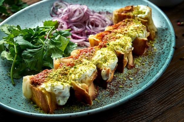 A classic turkish dish is sliced shawarma with chicken kebab topped with red and white pistachio sauce, served in a blue plate on a wooden table. restaurant food Premium Photo