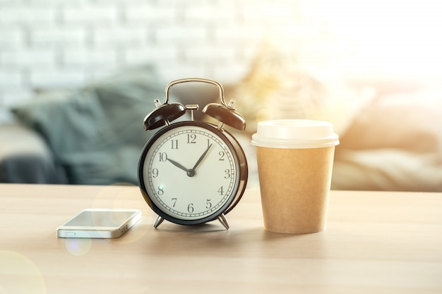 Classic vintage  alarm clock and  coffee cup on wooden background Premium Photo